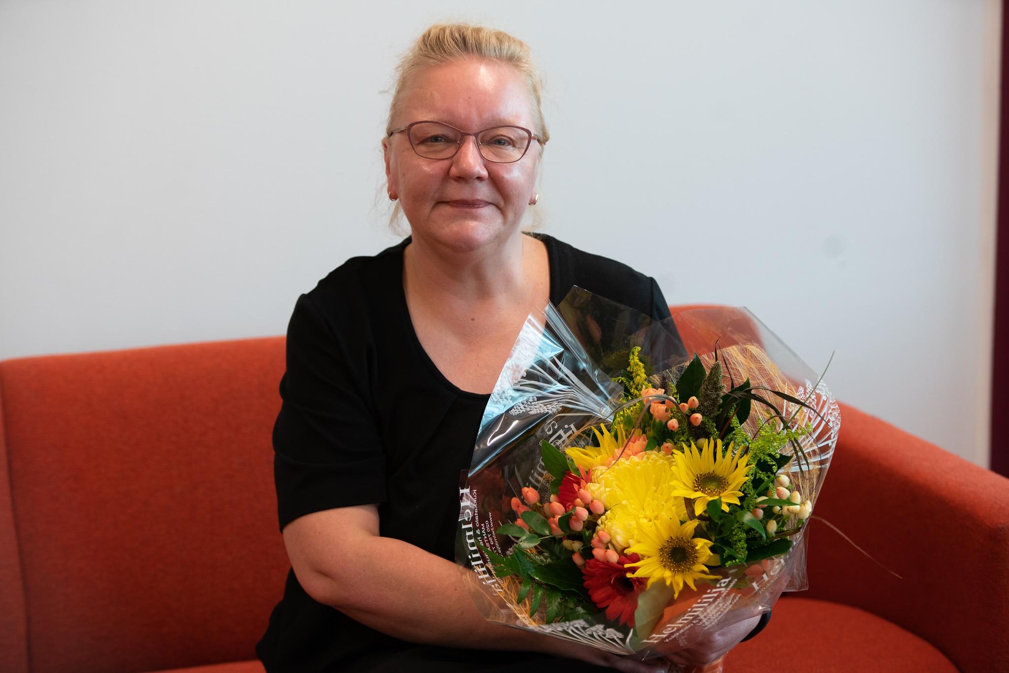 Kaupan alan vuoden 2020 työpaikkaohjaajana palkittu Maarit Holopainen istuu sohvalla kukkakimppu kädessä.